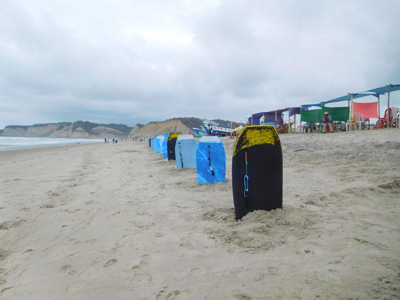 Wellenbretter und kleine Buden mit Liegestühlen stehen zwischen den Fischerbooten