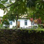 mit Mauer vor dem Haus und Rüschengardinen am Fenster